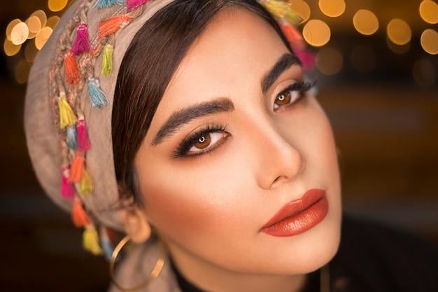 Modelo femenino en cubierta de cabeza de estilo étnico con aspecto romántico