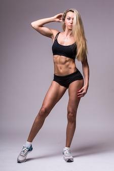 Modelo femenino de fitness en ropa deportiva sobre fondo gris