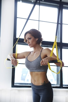 Modelo femenino haciendo actividades deportivas en el gimnasio.
