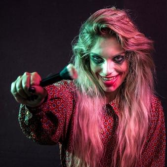 Modelo femenino de halloween con un cepillo de polvo
