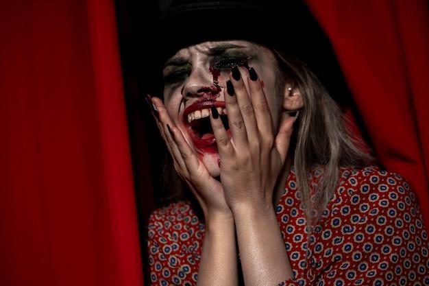 Modelo femenino de halloween riendo con los ojos cerrados
