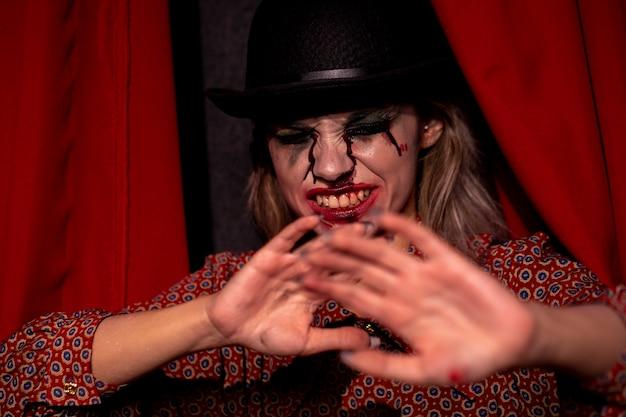 Modelo femenino de halloween sosteniendo sus manos delante de ella