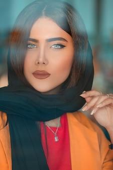 Modelo femenino en hijab negro y chaqueta naranja
