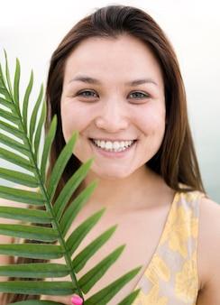 Modelo femenino joven asiático y hoja tropical