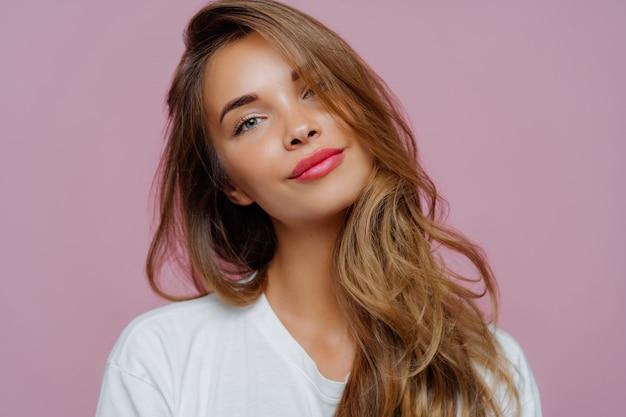 Modelo femenino joven relajado inclina la cabeza, tiene maquillaje, cabello rubio, vestida con ropa blanca