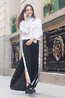 Modelo femenino joven sonriente que camina en la acera que habla en el teléfono móvil