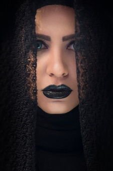 Modelo femenino en mantón de encaje gótico y lápiz labial morado