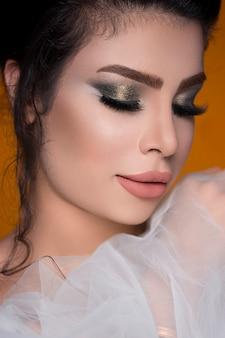 Modelo femenino en maquillaje de ojos ahumados y con lápiz labial rosa