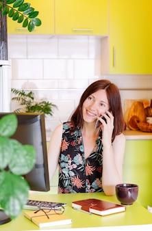 Modelo femenino en la oficina en casa usando su computadora y tomando café