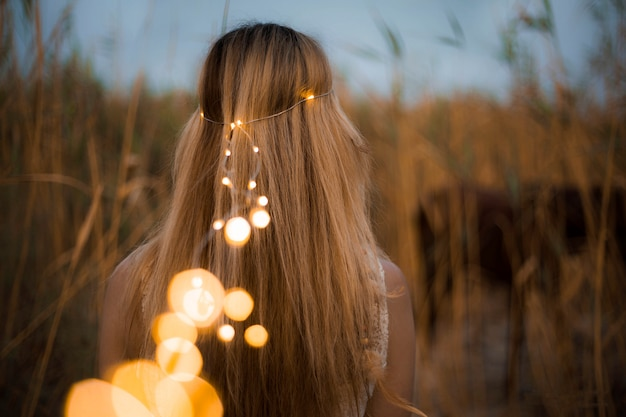 Modelo femenino con perlas de iluminación en la naturaleza