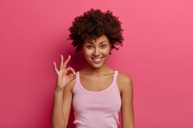 Modelo femenino de piel bastante oscura muestra gesto bien