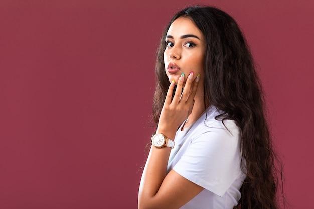Modelo femenino posando en la pared rosa
