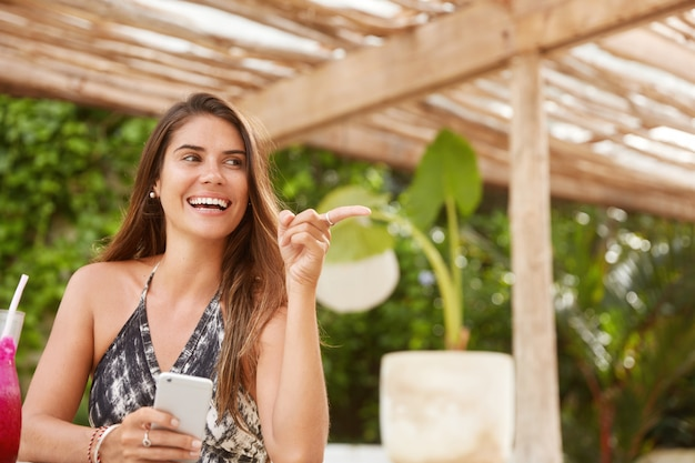 Modelo femenino positivo alegre recrear en cafetería al aire libre, batido de bebidas, tiene teléfono inteligente, conectado a internet inalámbrico, navega por las redes sociales. personas, ocio, concepto de comunicación