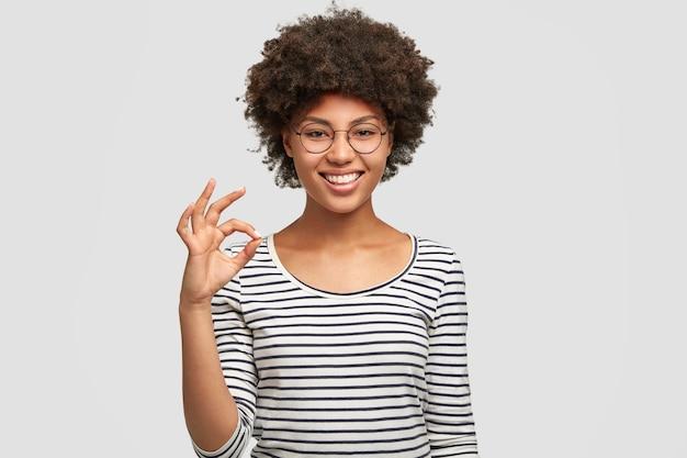 Modelo femenino de raza mixta positiva tiene peinado afro
