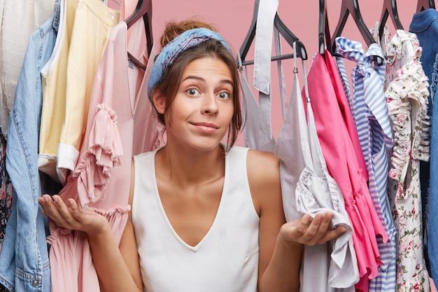 Modelo femenino en ropa casual, encogiéndose de hombros mientras está de pie cerca de su armario, dudando qué ponerse. mujer bonita que no tiene nada que ponerse. concepto de ropa y gente de moda
