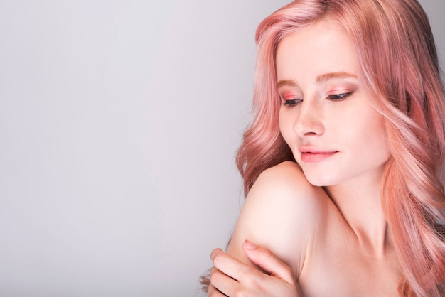 Modelo femenino sosteniendo su brazo con espacio de copia