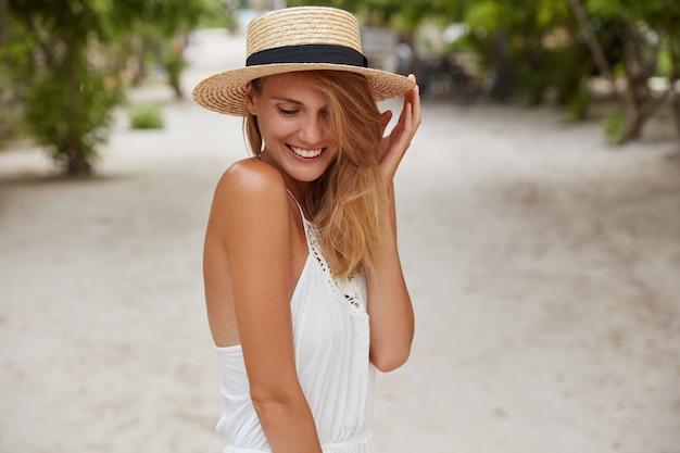 Modelo femenino tímido positivo con sombrero y vestido de moda, tiene una sonrisa agradable, mira hacia abajo con expresión feliz, posa al aire libre contra tropical