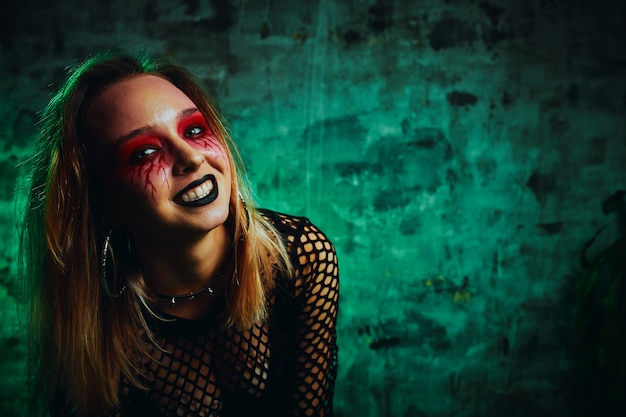 Modelo femenino en traje de halloween posando sobre un fondo rojo. hermosa chica en ropa celebra el día de los muertos. concepto de halloween, disfraz de bruja, colores brillantes, steam punk.