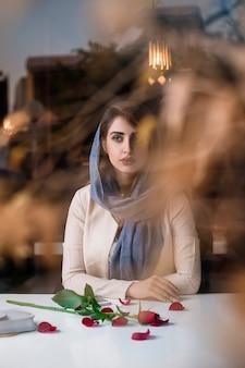 Modelo femenino en trajes de entrenamiento de moda hijab, vista desde la ventana