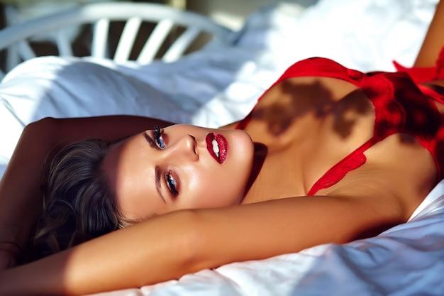 Modelo femenino vistiendo lencería roja en la cama por la mañana