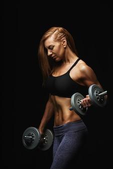 Modelo de fitness atractivo con pesas posando sobre un fondo oscuro en ropa deportiva