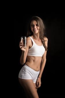 Modelo de fitness femenino sosteniendo un vaso de agua