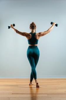 Modelo de fitness hermosa haciendo ejercicios con pesas en las manos. la niña practica deportes en el gimnasio sobre un fondo gris.