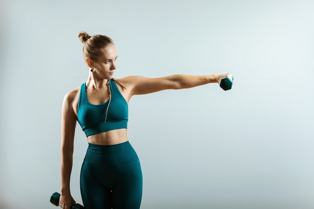 Modelo de fitness hermosa haciendo ejercicios con pesas en las manos sobre un fondo gris.