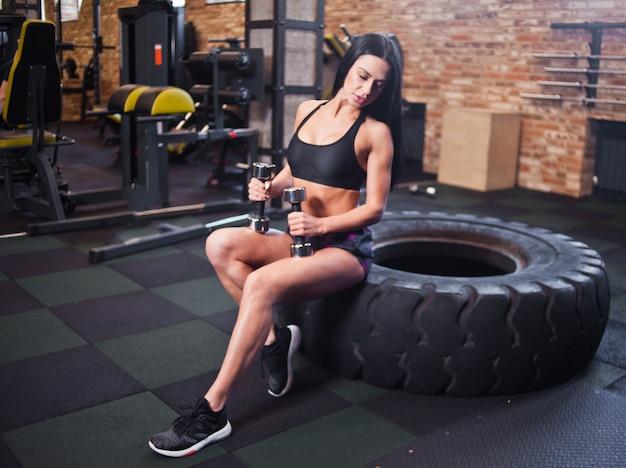 Modelo de fitness sexy sosteniendo pesas en las manos y sentado en la rueda grande en el gimnasio