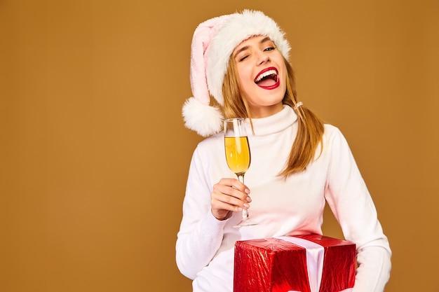 Modelo con gorro de papá noel y caja de regalo grande bebiendo champán en la pared de oro