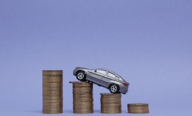 Un modelo gris de un automóvil con monedas en forma de histograma en violeta