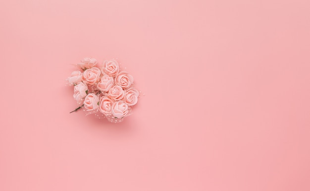 Modelo hecho de flores rosadas en fondo rosado.