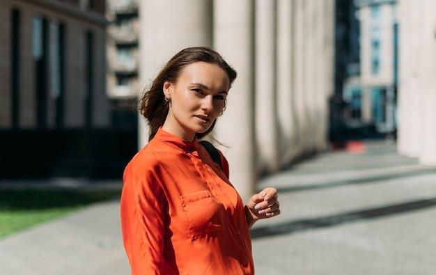 Modelo hermosa chica posando en la cámara en la ciudad de verano bajo el sol