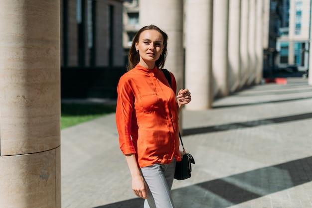 Modelo hermosa chica posando en la cámara en la ciudad de verano