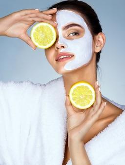 Modelo hermosa divertida con rodajas de limón hasta los ojos