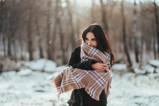 Modelo hermoso joven que presenta en bosque del invierno. elegante retrato de moda
