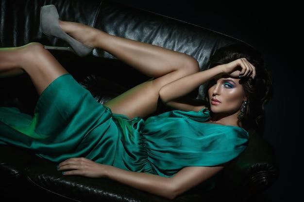 Modelo en hermoso vestido verde posando en el sofá de cuero