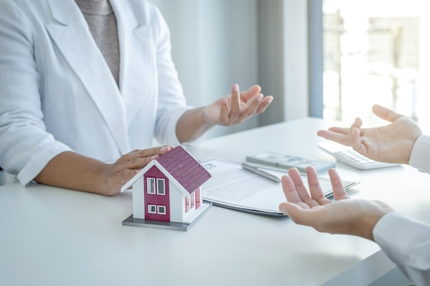 Modelo de hogar. el agente inmobiliario explica el contrato comercial a la mujer compradora.