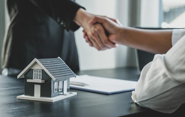 Modelo de hogar. los agentes inmobiliarios y los compradores se dan la mano después de firmar un contrato comercial.
