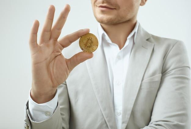 Modelo de hombre guapo en un traje gris de moda tiene un bitcoin