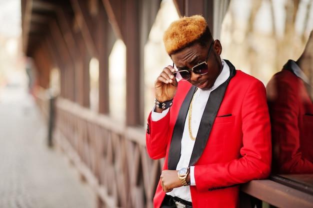 Modelo de hombre de moda en traje rojo, con reflejos de cabello en la calle.