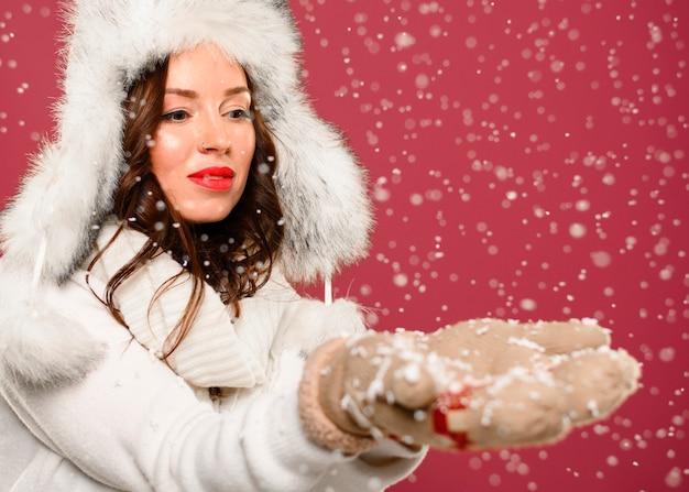 Modelo de invierno de moda cogiendo copos de nieve