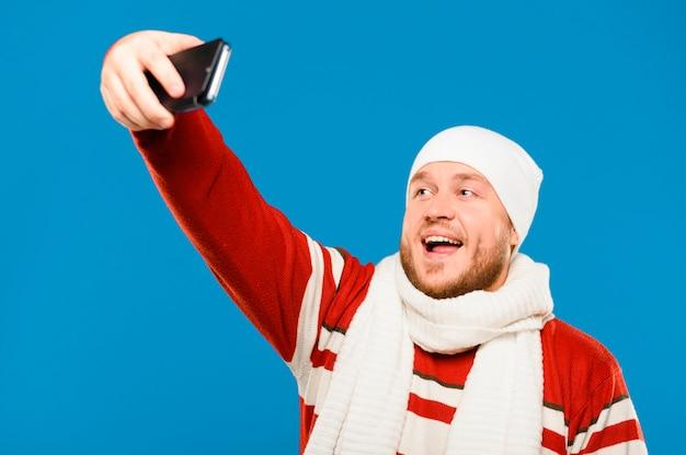 Modelo de invierno tomando una selfie