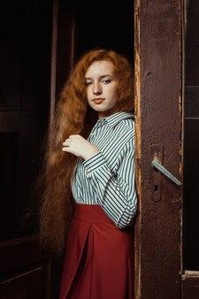 Modelo de jengibre joven triste con exuberante cabello rojo y pecas de pie en las puertas antiguas