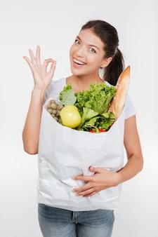 Modelo joven en camiseta con paquete de comida en estudio