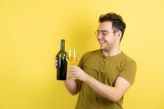 Modelo joven con copa y botella de vino blanco.