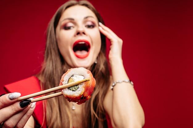 Modelo joven morena con el pelo largo comiendo comida asiática.