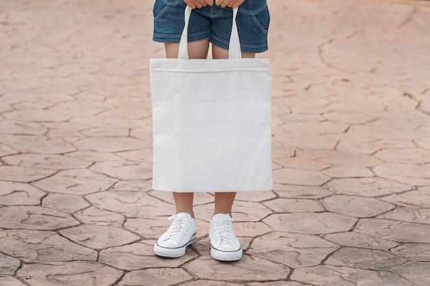 Modelo joven que sostiene la bolsa de asas blanca para la plantilla en blanco de la maqueta