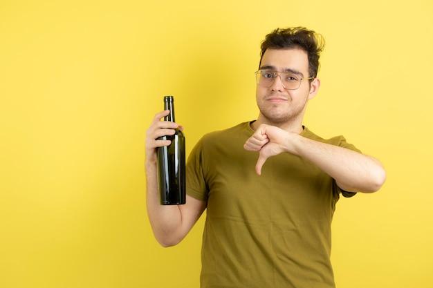 Modelo joven sosteniendo una botella de vino blanco y dando pulgares hacia abajo.