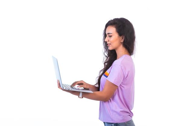 Modelo joven sosteniendo una computadora portátil plateada y con videollamada, vista de perfil.